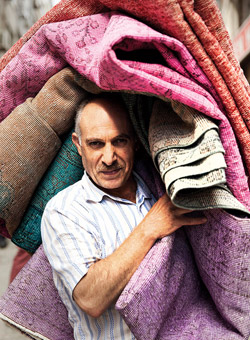 man carrying turkish rugs